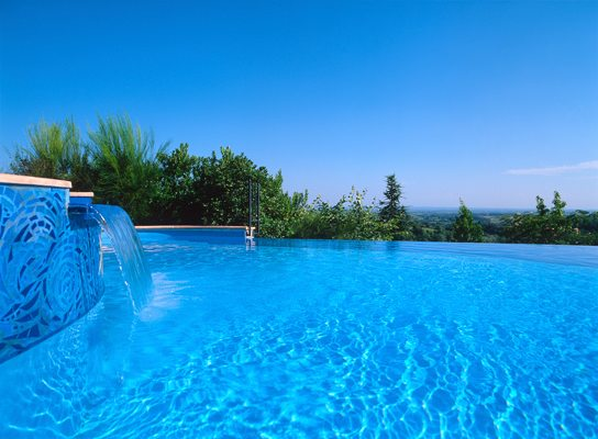 Outdoor flush edge swimming pool with blue sky on the background