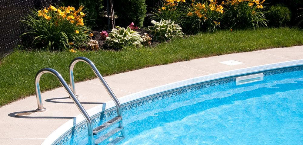 An outdoor backyard pool featuring above ground pool entry steps. If you have an above ground pool, or are thinking about installing one, you'll need to consider which above ground pool entry steps to choose.