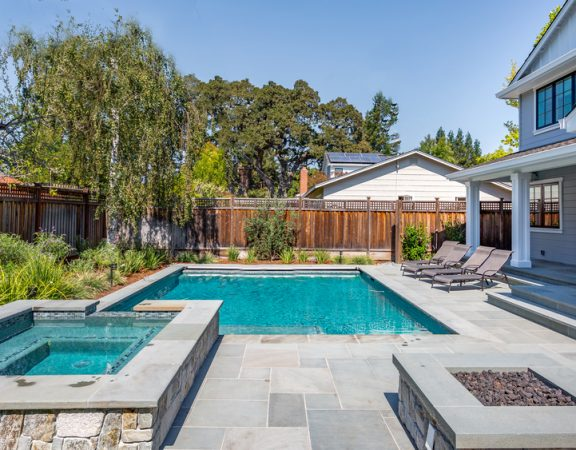 A beautiful backyard pool surrounded by tall fences and shrubbery. Are you looking for ways to build up your backyard privacy from peering eyes? Here are some ideas to get you started!